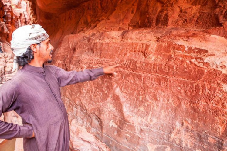 bedouin explains inscriptions in wadi rum