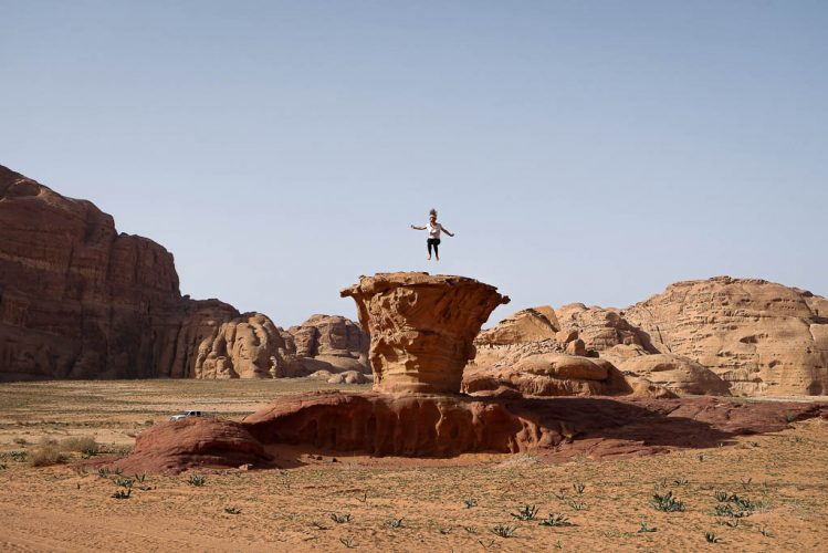 skinny mushroom rock in wadi rum desert with tourist jumping on top