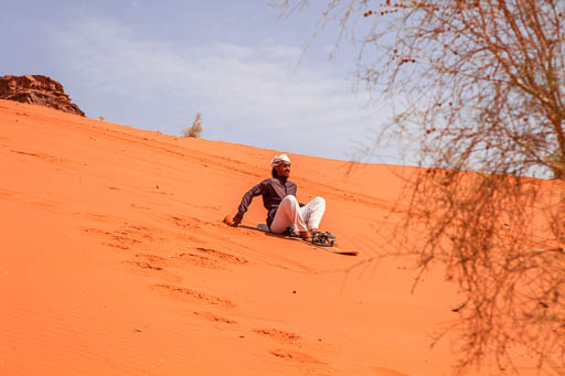 Bedouin sitting on sandboard enjoying sand dunes in Wadi Rum