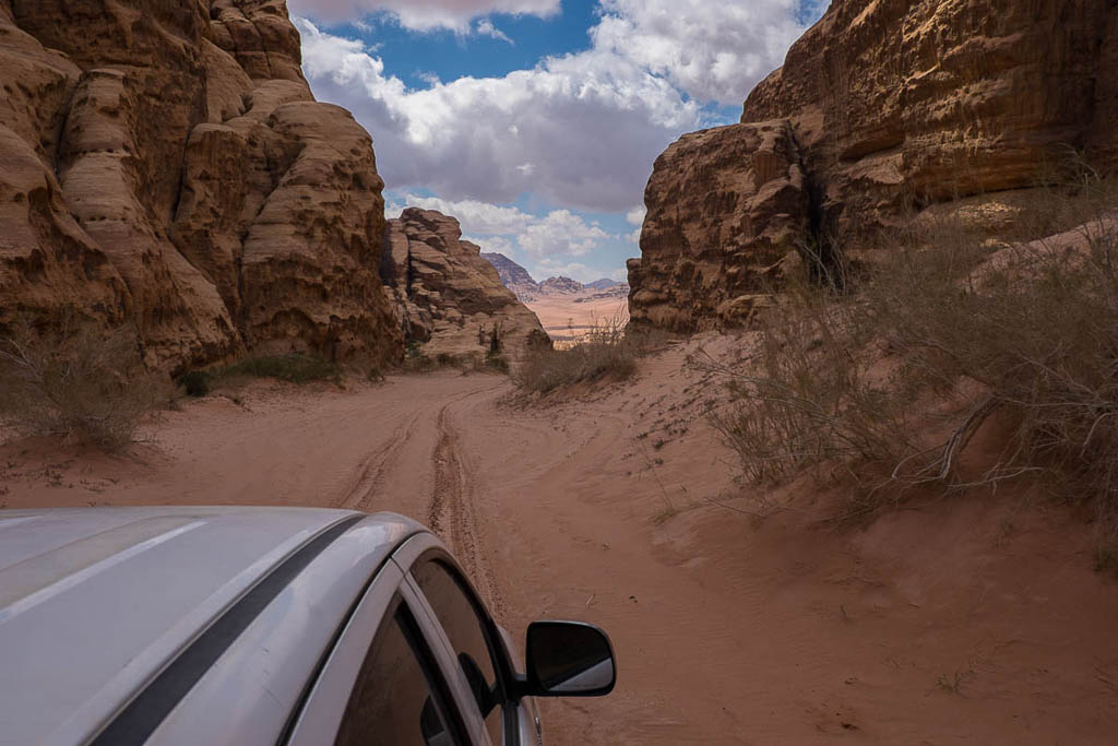jeep driving through narrow canyon in wadi rum desert