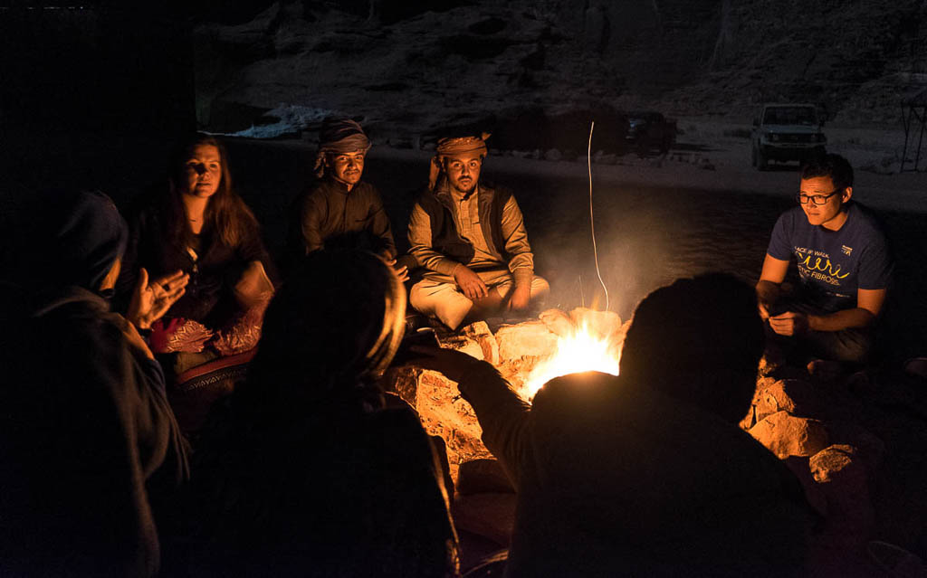bedouin around campfire with tourists wadi rum