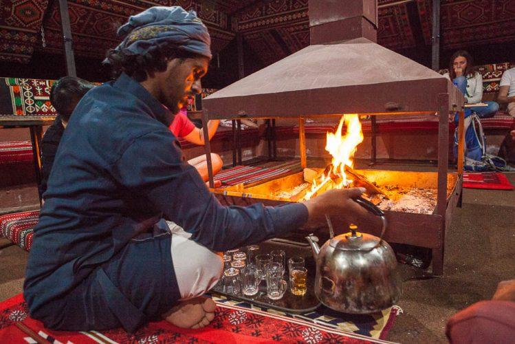 bedouin pours tea by campfire in bedouin camp in wadi rum