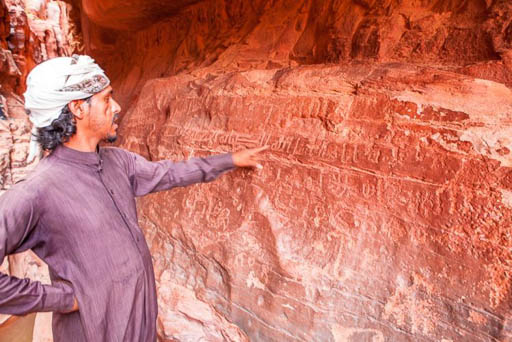 bedouin reads insciptions in wadi rum
