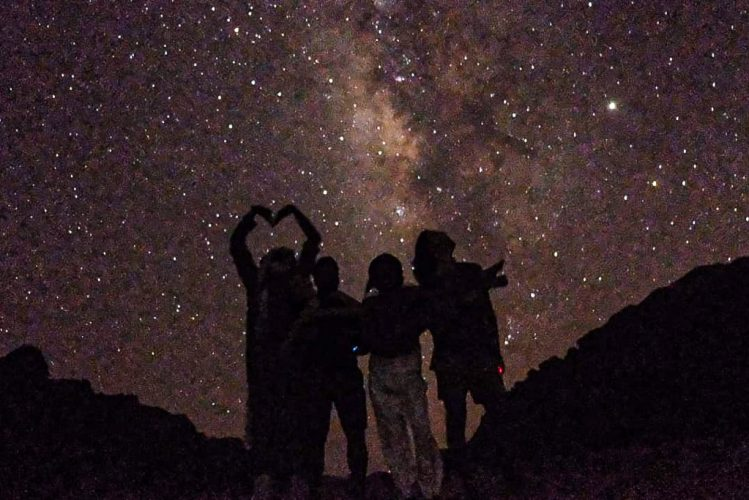 silhouette of tourists enjoying stars in Wadi Rum on warm desert night