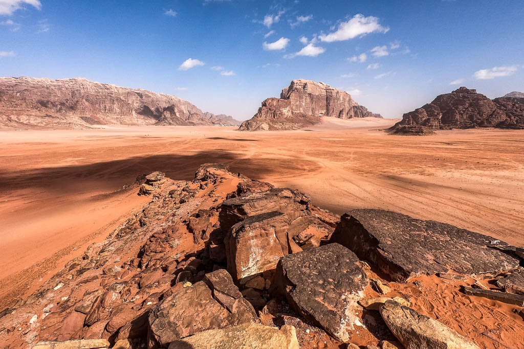 clouds cast shadows over wadi rum desert with red sand and rocky cliffs