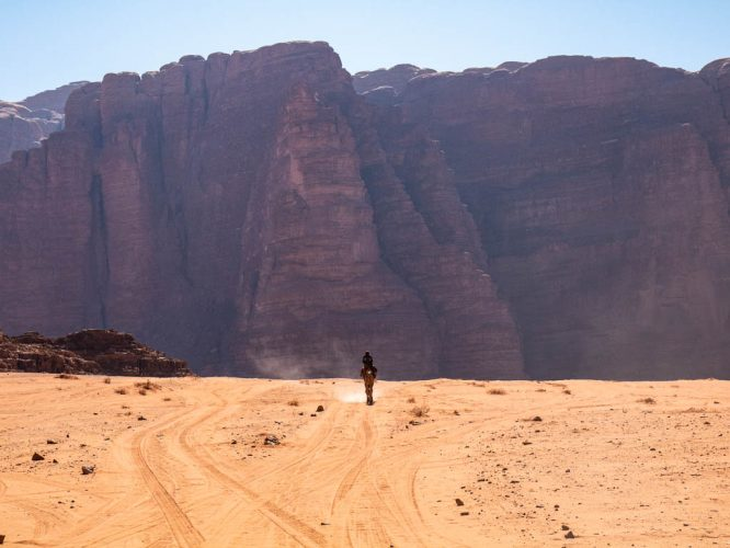 Bedouin riding lone camel through the desert, Wadi Rum