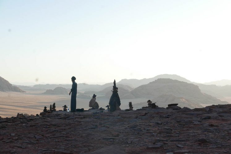 bedouin looks over valley in wadi rum as sun rises early in the morning