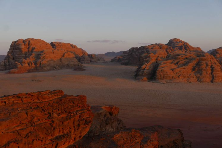 cliffs turn red as the sun sets in wadi rum desert jordan