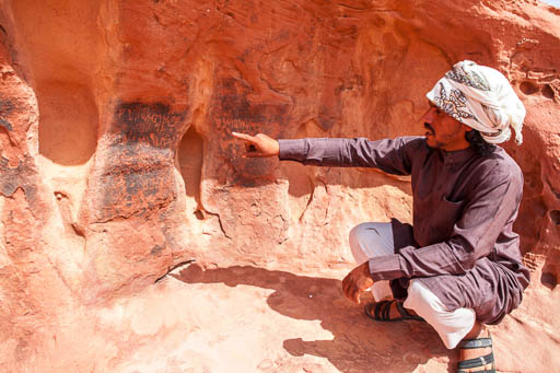 Wadi Rum inscriptions with bedouin explaining