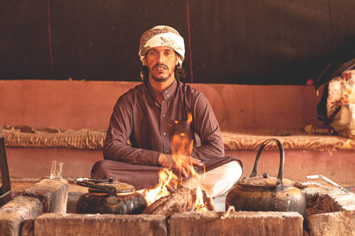 bedouin sitting in front of fire