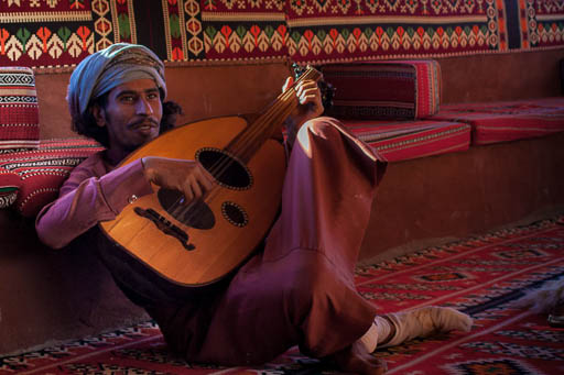 bedouin playing oud in room with traditional fabrics