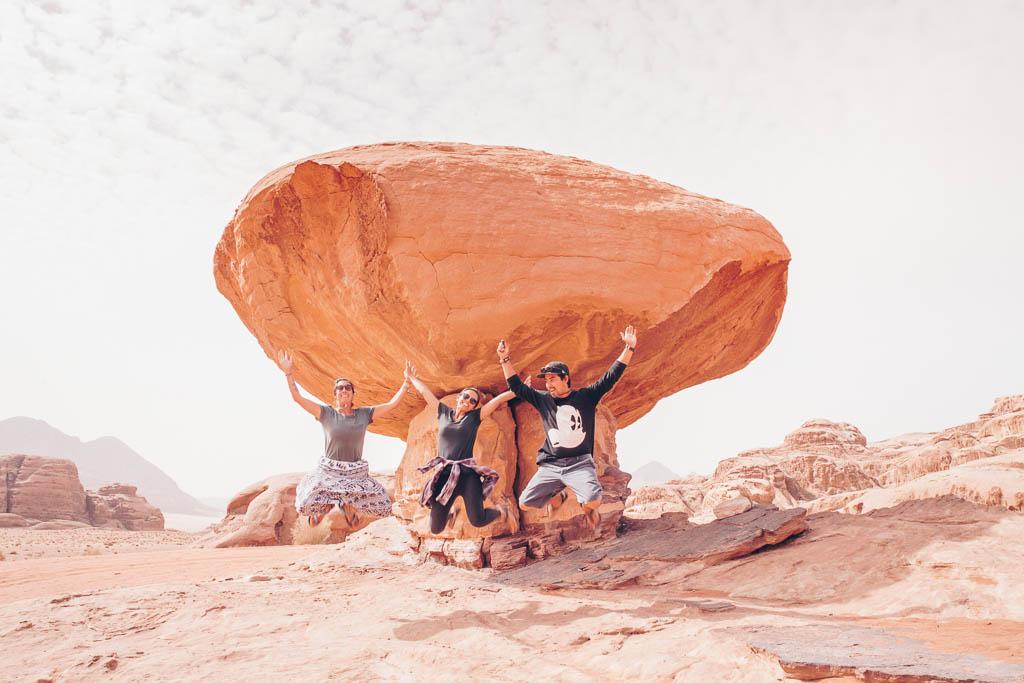 tourists jump infront on mushroom rock wadi rum